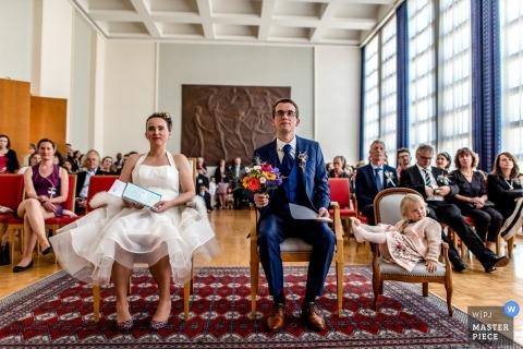 Brest, Frankrijk de foto van de huwelijksceremonie van bruid, bruidegom en bloemmeisjezitting als voorzitter met gasten achter hen.