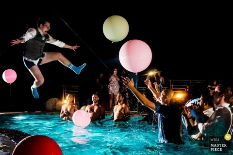 Croatia wedding picture of groomsman jumping into pool with socks on.