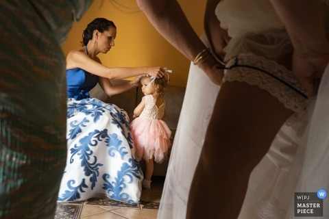 Valencia wedding picture of the bride putting on her garter as the flower girl has her hair fixed.