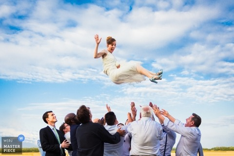 Paris wedding portrait of the bride being tossed into the air.