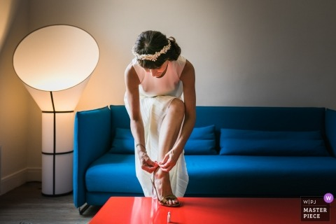 Paris wedding picture of the bride fastening her shoes on the table.