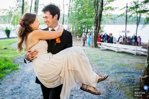 New York wedding picture of the groom carrying the bride after outdoor reception in the woods.