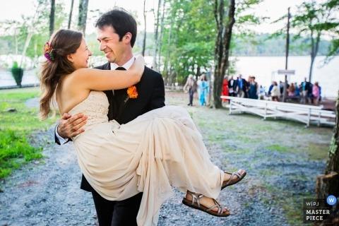 Imagen de la boda de Nueva York del novio que lleva a la novia después de la recepción al aire libre en el bosque.