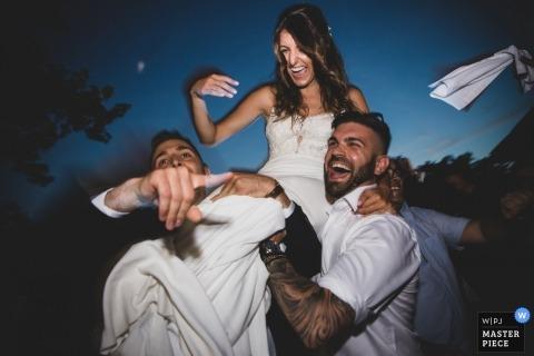 Lucca-Hochzeitsbild der Braut, die draußen auf die Schultern von Kerlen reitet.