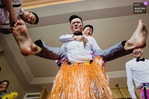 Sanya wedding picture of Chinese door games for groom and his friends in grass skirts.