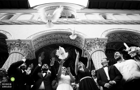 Bride and groom let go of birds after the ceremony in Bucuresti