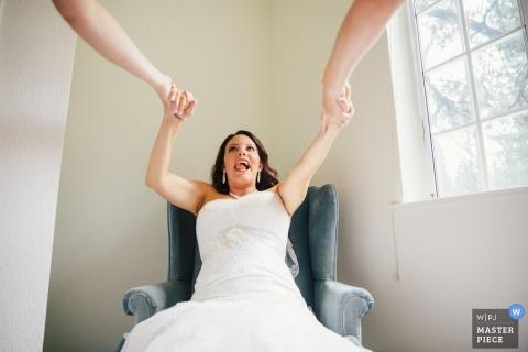 South Lake Tahoe, CA trouwfoto van de bruidsmeisjes die de bruid uit een stoel helpen.