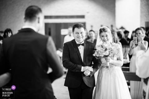 Neuchâtel, Suisse, photo de mariage des mariés établissant un contact visuel pendant qu'elle se promène dans l'église avec son père.