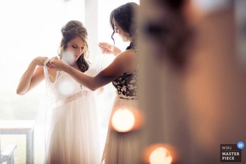 Fribourg, Suisse, photo de mariage de la mariée qui enfile sa robe.
