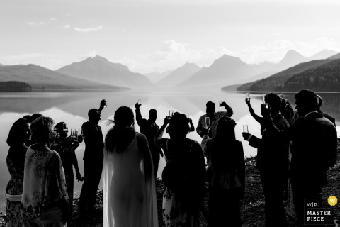 Glacier Park, Montana elopement wedding photograph of the bride and groom toasting with guests.