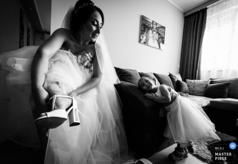 Svilengrad, Bulgaria wedding picture of bride putting on her shoes as a flower girl watches.
