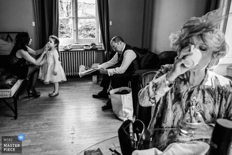 Lyon, Francia foto de boda de mamá bebiendo café mientras se aplica maquillaje a flowergirl.