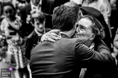 Sainte Colombe en Bruilhois, France wedding picture of groom getting kissed at ceremony by grandfather.