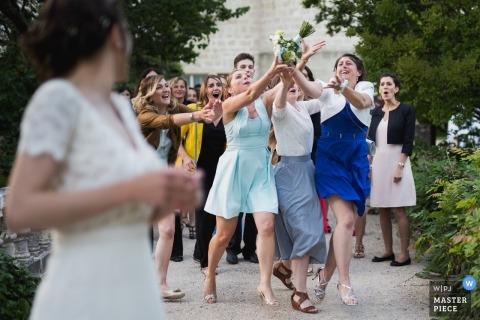 Grignols, Frankrijk trouwfoto van de vrijgezelle dames die springen om het bruidenboeket van bloemen te vangen.