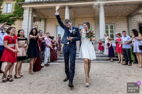 Paris wedding picture of the bride and groom walking past rice tossing guests.