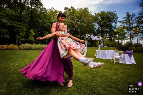 Het huwelijksbeeld van Boedapest van meisjes die buiten op het gras bij de ontvangst spelen.