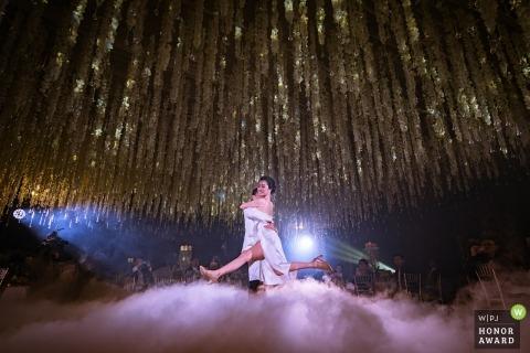 Bruid en bruidegom dansen op een mistige dansvloer in Bangkok