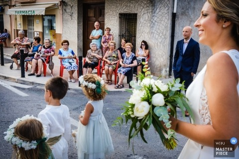 Benimarfull wedding picture of the bride walking with the flower girls and boy in the streets.