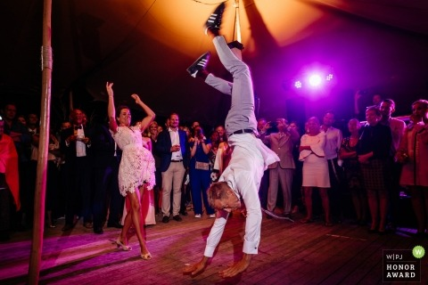 Gent groom does a hand stand on the dance floor