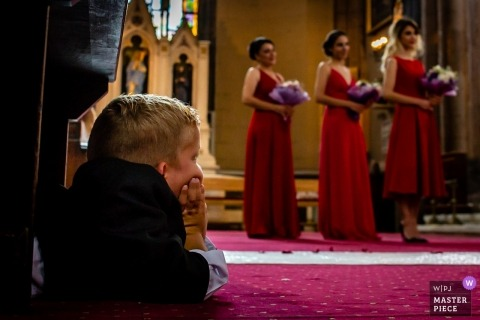 Istanbul, Turkey wedding picture of a boy in a suit lying on the carpet watching the long ceremony.