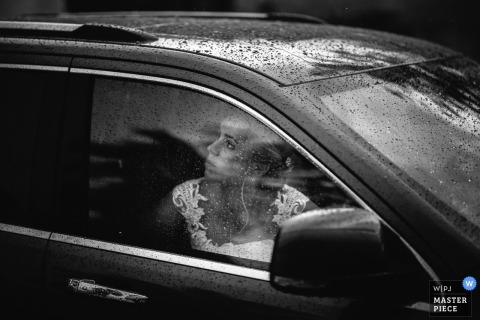 Alassio, Italy wedding image of the bride looking at the sky from the car covered with rain.