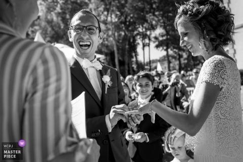 ChâteaudeSaintMarcàSaintNazaire婚禮照片的新郎在戶外儀式期間將戒指放在新娘的手指上。