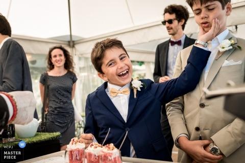ChâteaudeSaintMarcàSaintNazaire在婚禮招待會期間在甜點站玩耍的男孩的婚禮照片。