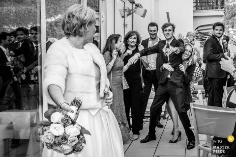 薩瓦的婚禮照片的新娘即將把她的花束扔給等候的客人。