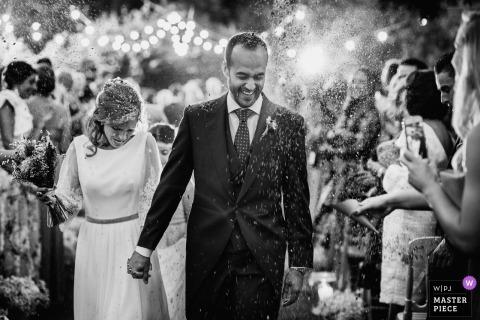 Photo de mariage à Toledo de la mariée et du marié se promenant dans des confettis / riz.