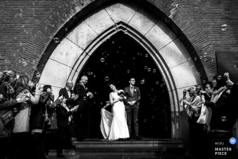 Antwerpen Wedding Photojournalism | the guests blow bubbles for the bride and groom as they exited the church after the ceremony