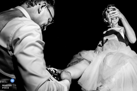 Antwerpen Wedding Photojournalism | the bride holds her drink as the groom helps with her shoes
