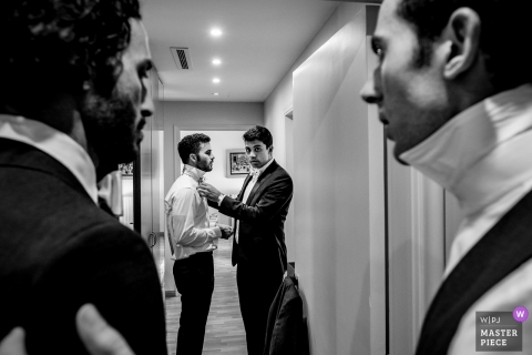 Beirut Wedding Photojournalism | Hotel hallway Final fixes for the grooms tie