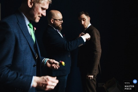 London Wedding Photojournalism | the bridal party helps each other attached boutonniere's to their suit coats