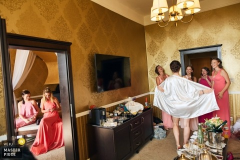 Slovakia Wedding Photojournalism | the bride shows off her new robe to the bridesmaids