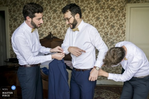 Nantes Wedding Photojournalism | the groom is helped with the buttons on his shirt as he is getting ready