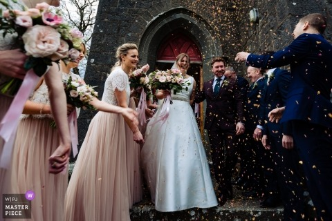 Dublin Wedding Photojournalism | wedding guests throat confetti over the bride and grooms head as they leave the church