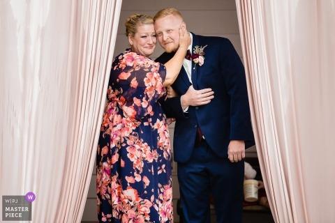 Spokane, WA Photojournalisme de mariage | le marié prend la mère dans ses bras alors qu'il se prépare à entrer dans la cérémonie