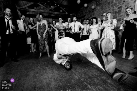 Laois Wedding Photojournalism | black-and-white reception image of a breakdancing guest