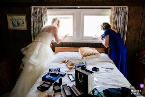 Chaumont, NY Wedding Photojournalism | in haar bruidsjurk kijkt de bruid vanuit de slaapkamer uit het raam