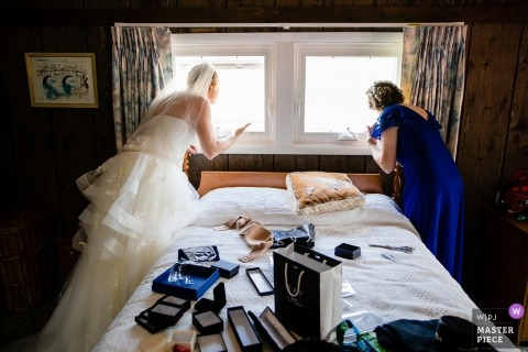 Chaumont, NY Wedding Photojournalism | in her wedding gown, the bride looks out the window from the bedroom