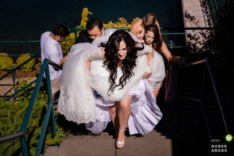 Hayden Lake, Idaho bride climbing outdoor stairs and getting help with her dress