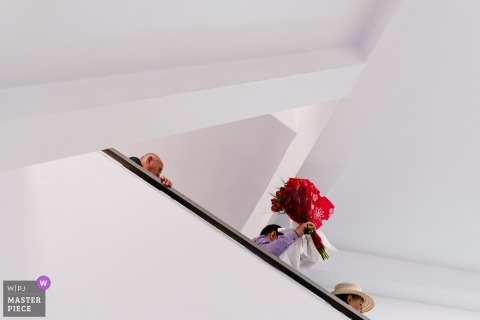 București Wedding Photojournalism | Bouquet of red Is escorted down the stairs