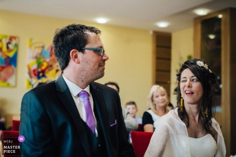 Nantes Wedding Photojournalism | the bride winks at the groom in this ceremony photo