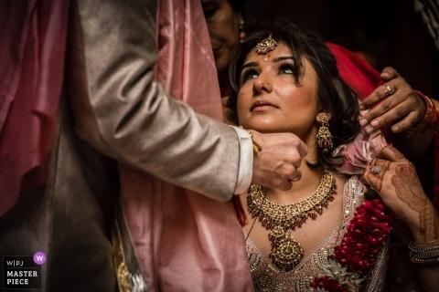 Groom placing necklace around his Hindu Bride's neck - Delhi, India