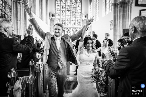 Somerset Wedding Photographer - Triumphant Couple walking down the aisle together - North Cadbury Court