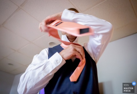 Granville, OH Wedding Photojournalism | slow shutter Picture of a groomsman tying his tie