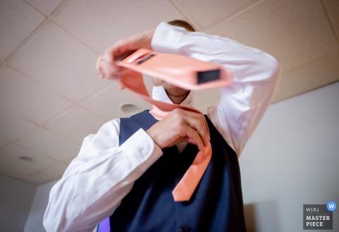 Fotogiornalismo di nozze di Granville, OH | scatto lento Immagine di un groomsman che si lega la cravatta