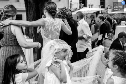 Cumiana Wedding Photojournalism | Young girls play under the covering of the brides dress train