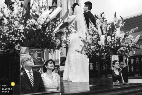 Igreja Santo Antônio Sete Lagoas wedding photograph of parents reflected in mirror watching bride and groom during ceremony.