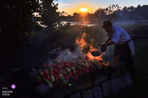 Kennebunkport, Maine Wedding Photojournalism | outdoor wedding reception food preparation on open fire